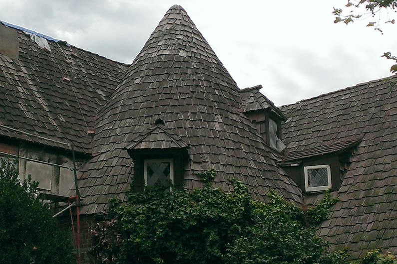 Damaged cedar shake roof prior to slate roof replacement