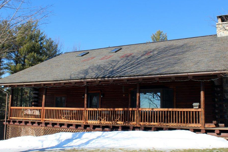 Log home with natural slate roof. The year 2001 was detailed on the roof with red slate.